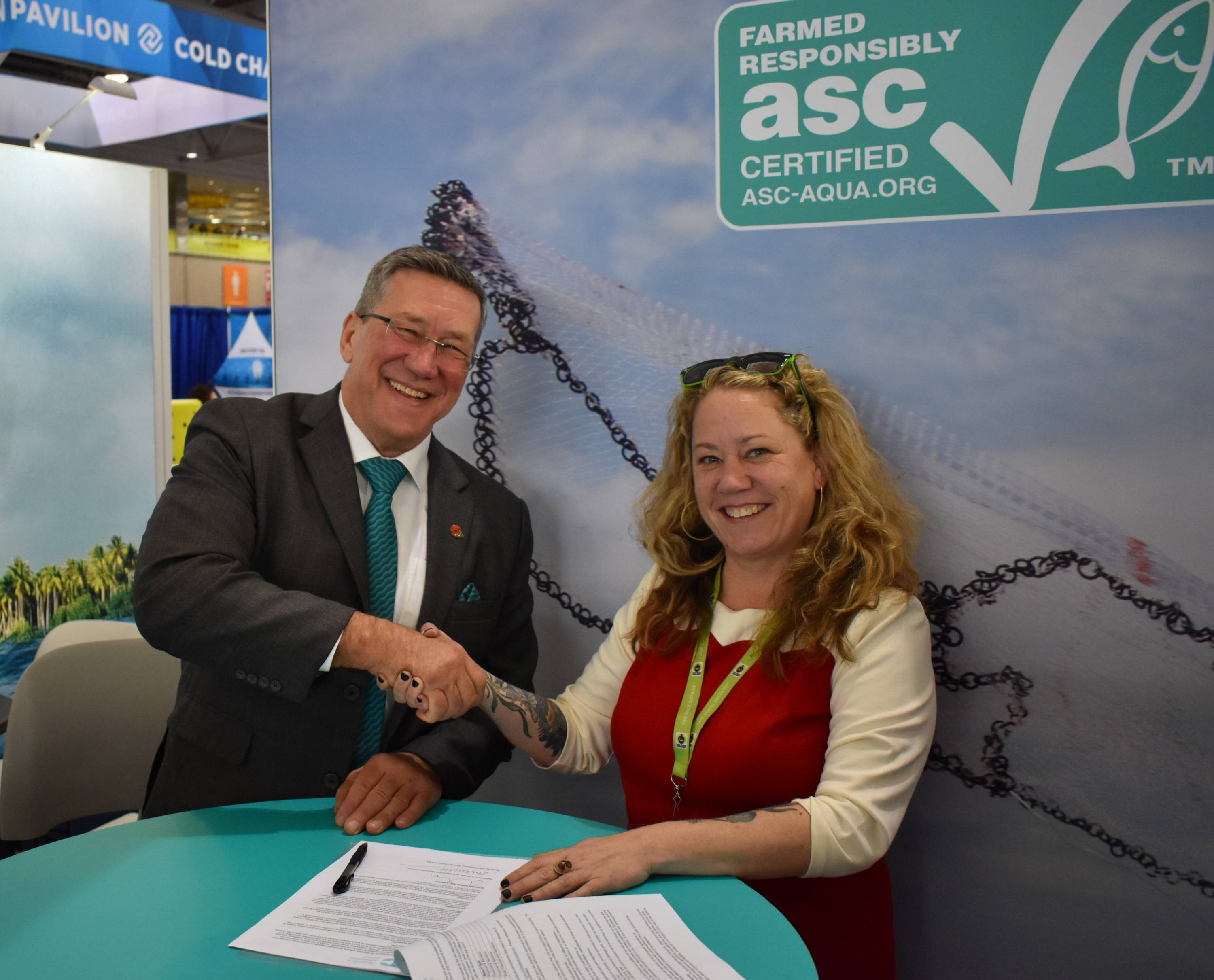 Chris Ninnes, CEO of ASC and Julie Kuchepatov, Director, Seafood at Fair Trade USA shake hands after signing the MOU at the ASC stand at the 2019 Seafood Expo North America in Boston