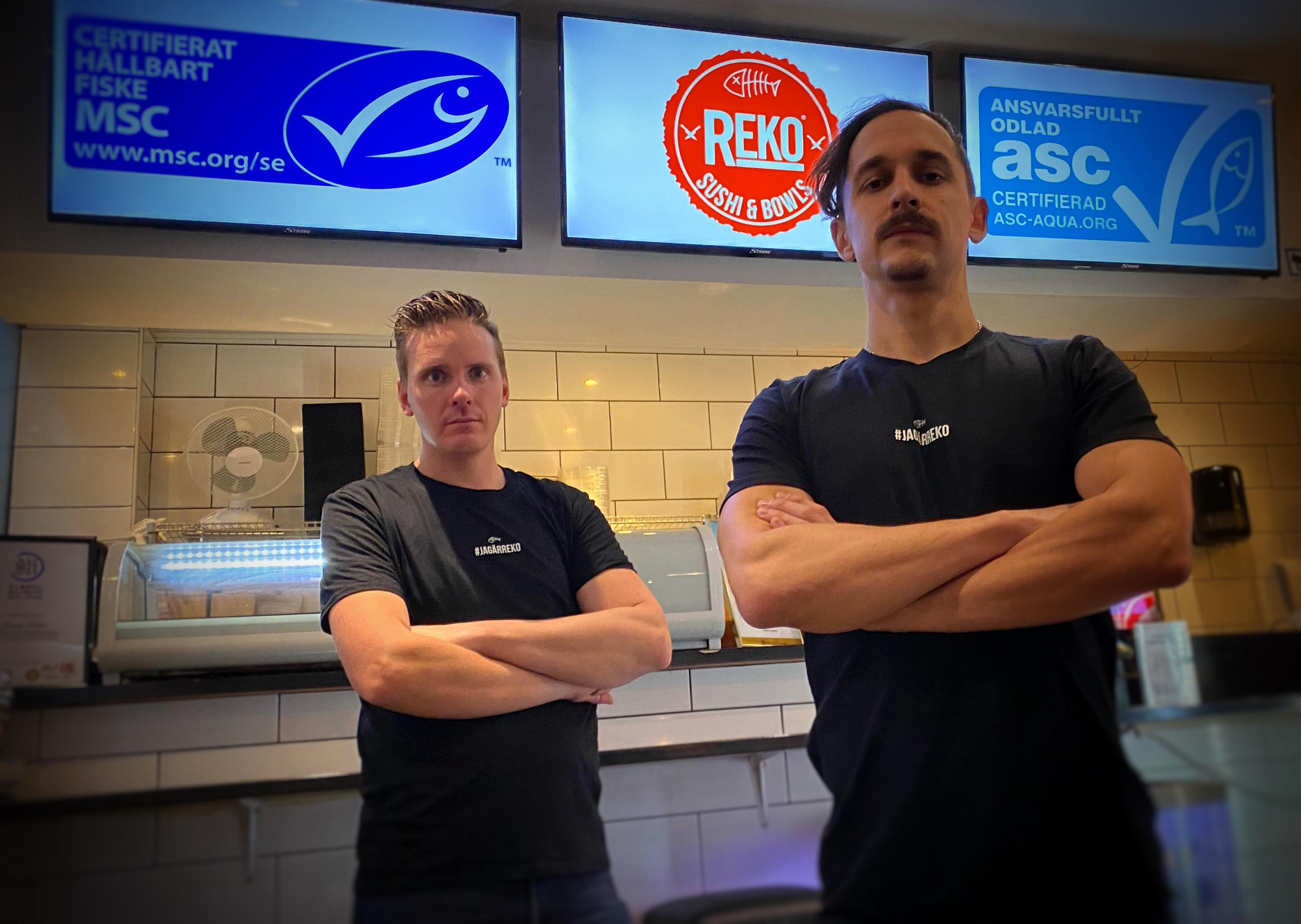 The founders of Reko Sushi and Bowls stand behind the counter of one of their restaurants with ASC and MSC logos on screens behind them